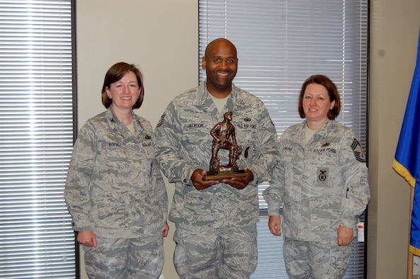 NELLIS AIR FORCE BASE, Nev. -- (Center) Tech. Sgt. Dwayne Jackson, 926th Group antiterrorism officer and security manager, is presented with the Air Force Reserve Command's Security Forces Staff Noncommissioned Officer of 2010 award by Col. Mary Roehl, AFRC's Top Cop, and Chief Master Sgt. Suzanne Clemons, AFRC's chief of training and combat arms, here April 1. (U.S. Air Force photo/Capt. Jessica Martin)