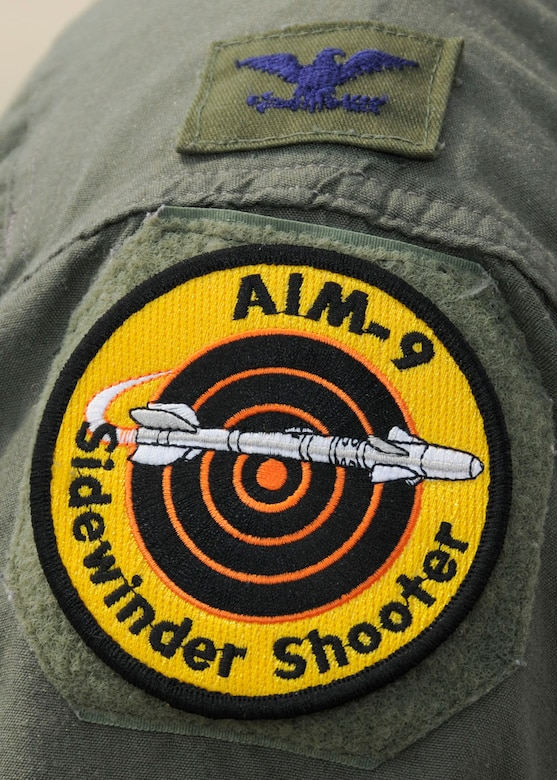 A newly achieved AIM-9 Sidewinder Shooter patch worn my Col. Kenneth Lambrich from the 104th Fighter Wing, Massachusetts Air National Guard as he watches maintenance crews work on the F-15 at Tyndall AFB, Florida as they participate in the Weapons System Evaluation Program (WSEP), known as Combat Archer, on April 19, 2011. This training is important for the ground crews to test their maintenance systems and processes while loading live munitions on the F-15 eagle, as well as critical live war fighting training for the F-15 pilots to employ air-to-air missiles against real world targets.  (U.S.A.F. photograph by Senior Master Sgt. Robert J. Sabonis)