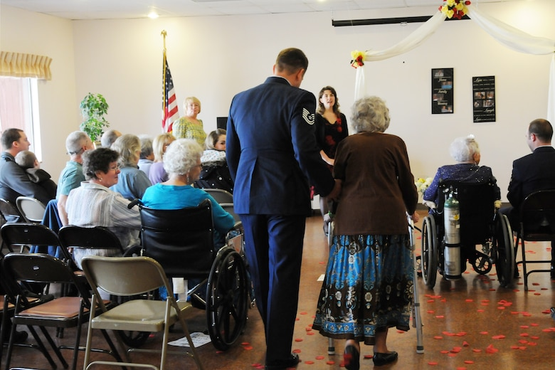 Tech. Sgt. Michael Shirar, 173rd Fighter Wing Maintenace Training Manager, escorts  Mrs. Irene Dalton, the 2011 Rose Queen Princess,to the stage during the ceremony.  Members of the Oregon Air National Guard volunteered to help with the 2011 Rose Queen Corenation ceremony at Plum Ridge Marquis Care in Klamath Falls, Ore. April 8, 2011. (U.S. Air Force Photo by Tech.Sgt. Jennifer Shirar, RELEASED)