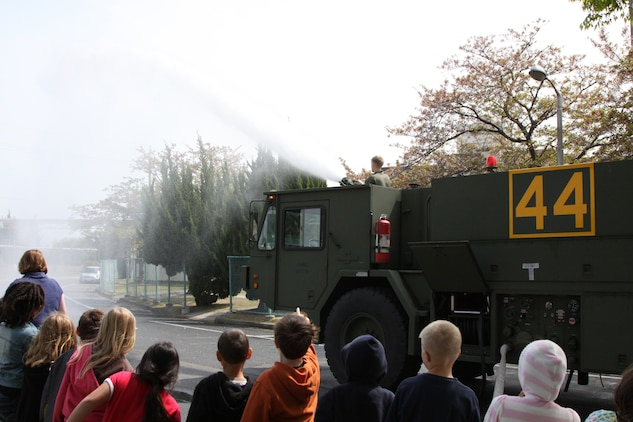 Students from Matthew C. Perry Elementary School raise their hands after Staff Sgt. Jason Nickell, aircraft rescue firefighter, asks if the students want to see the truck shoot water at M.C. Perry here April 21. Most fire trucks here hold approximately 300 to 400 gallons of water; however, the ARFF fire trucks hold up to 1,000 gallons.