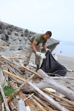Lance Cpl. David Reyesjimenez, Combat Logistics Company 36 engineer equipment mechanic, gathers trash and man-made debris along the seawall near Penny Lake during an Earth Day celebration here April 22.