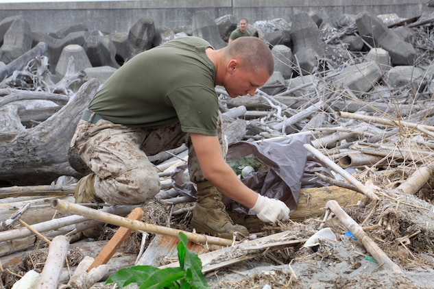 Lance Cpl. Nick Schiner, Combat Logistics Company 36 engineer equipment mechanic, gathers trash and debris along the seawall near Penny Lake during an Earth Day celebration here April 22. More than 80 Marines, sailors and station residents volunteered to clean the area around the seawall where the Nishiki River meets the Iwakuni harbor.