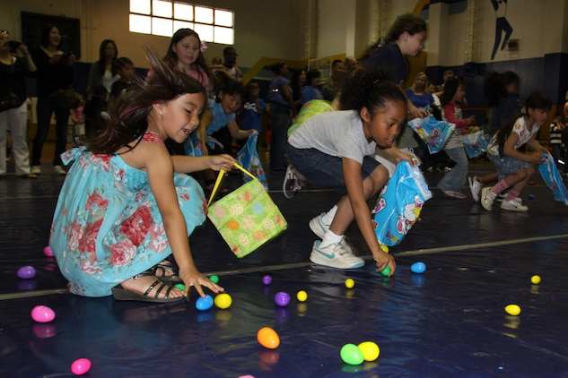 Nalia Kim, 7, and Keandra Conner, 7, Easter egg hunters, snatch colorful candy-filled eggs during the 8th annual Iwakuni Easter Egg Hunt at the IronWorks sports courts here April 23. As soon as Tera Scott, Youth and Teen Center program assistant, gave the word, the children went wild and scrambled to pile as many plastic eggs as they could into their baskets. The Youth and Teen Center hosted the event by providing goodie bags and more than 2,000 plastic eggs for children to collect in their Easter baskets.
