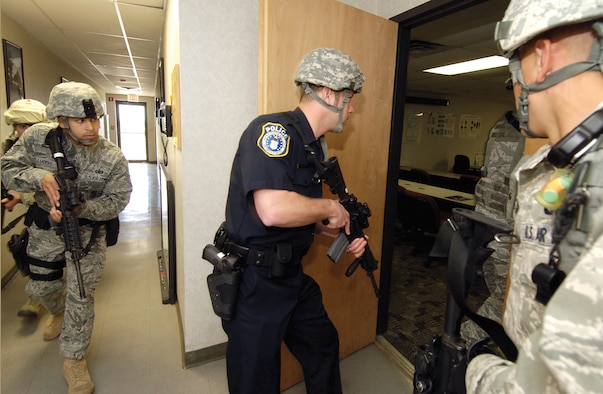 In a security forces building, Tinker 72nd Security Forces Squadron military and Department of Defense police train for responding to active shooter scenarios. (Air Force photo by Margo Wright)