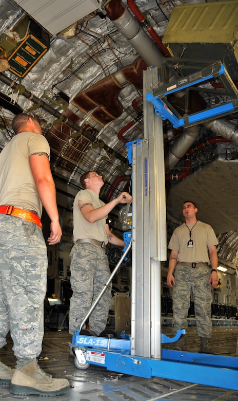 Senior Airman David Torres (left), Airman 1st Class Eric Duncan (middle) and Staff Sgt. Jessy Martin use a Genie lift to lower a 46-person life raft from the inside of a C-17 April 25, on Joint Base Charleston - Air Base. Each C-17 carries three life rafts that must be replaced every three years. Airman Torres, Airman Duncan and Sergeant Martin are crew chiefs from the 437th Aircraft Maintenance Squadron. (U.S. Air Force photo by /Airman 1st Class Jared Trimarchi)