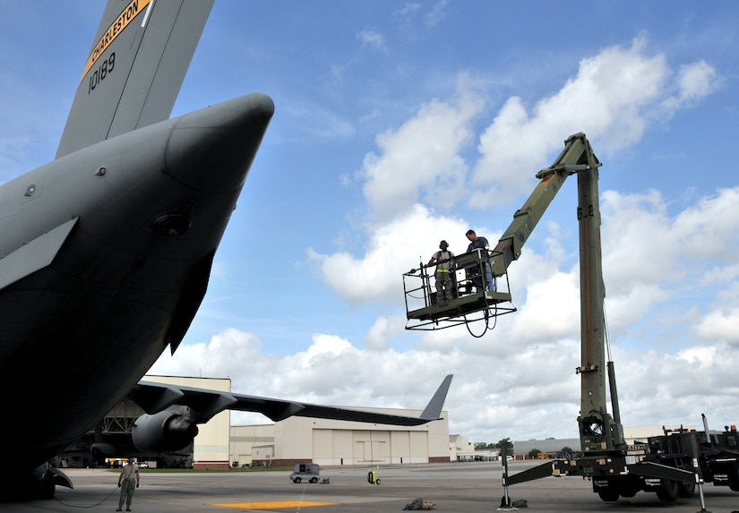 William Rigdon (right) and Senior Airman Charles Barnes, hydraulic technicians from the 437th Aircraft Maintenance Squadron, ride a high reach lift, or Condor, to the tail of a C-17 April 25, on Joint Base Charleston - Air Base. The technicians were thoroughly inspecting the Integrated Flight Control module. Airman Barnes is part of the 437 AMXS team Gold and Mr. Rigdon is part of team Blue. (U.S. Air Force photo by /Airman 1st Class Jared Trimarchi)