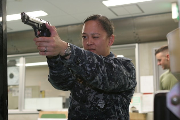 Navy Lt. Beverly J. Torres, a Robert M. Casey Medical and Dental Clinic staff nurse, zeroes in on a target at the Indoor Small Arms Range here April 27 during pistol qualifications. The course was offered over a three-day period and trained sailors on pistol grip and stance in relation to distance.