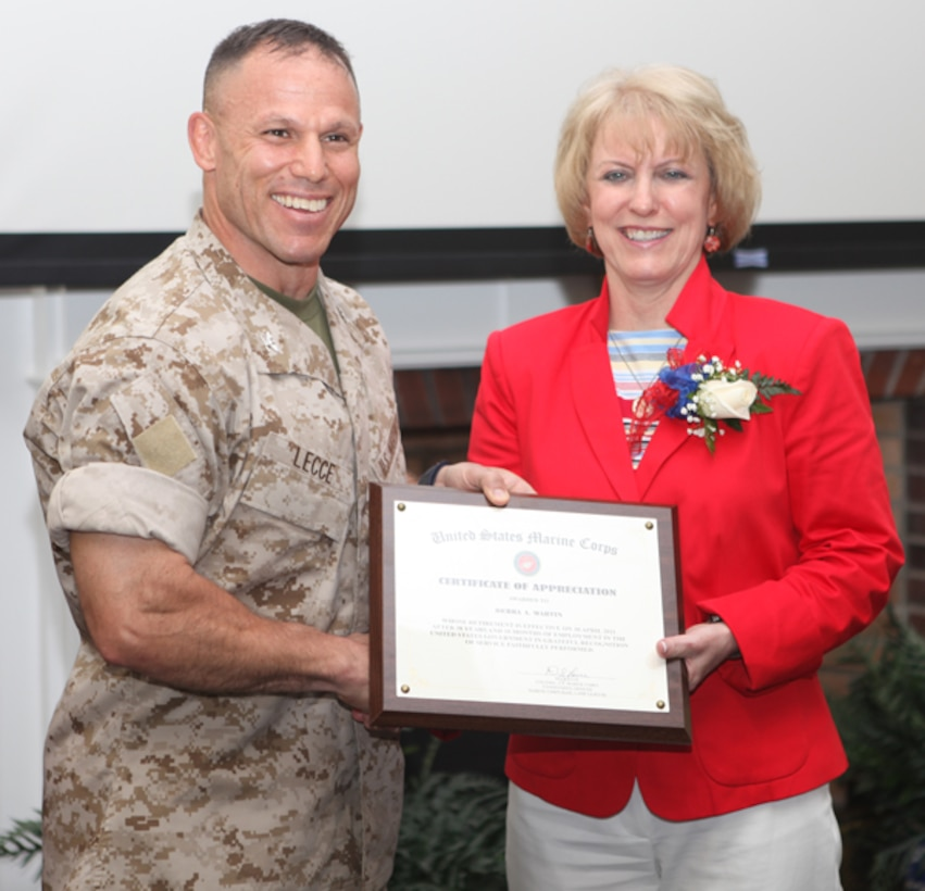 Col. Daniel J. Lecce, commanding officer of Marine Corps Base Camp Lejeune, presents Debbie Martin, supervisory management program analyst, with a certificate of appreciation during her retirement luncheon April 28. Martin retired April 30 after 38 years of civil service.
