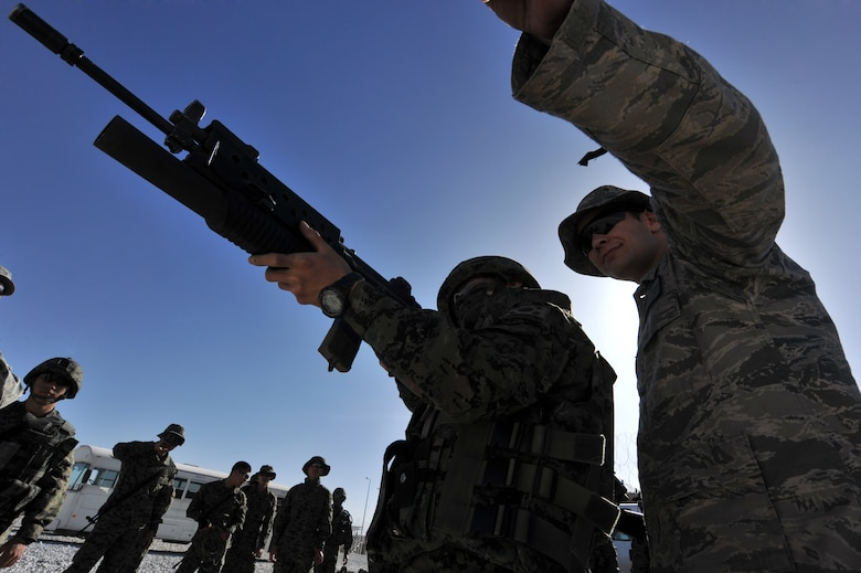 Senior Airman Gary Farmer, 455th Expeditionary Security Forces Squadron, watches Staff Sgt. Jon Myung Jae, Republic of Korean army security forces, fires a non-lethal 40mm sponge round during a M203 grenade launcher training at Bagram Airfield, Afghanistan, April 22, 2011. Members from the ROK army security forces have to qualify on a M203 grenade launcher before joining Bagram's base defense. (U.S. Air Force photo by Senior Airman Sheila Devera)