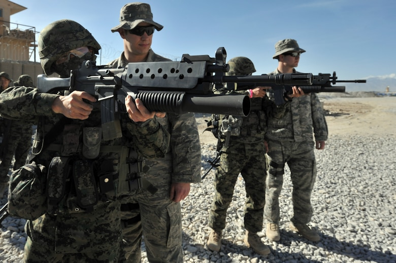 Senior Airman Gary Farmer (second from left) and Staff Sgt. Mason Flores, from the 455th Expeditionary Security Forces Squadron, watch Staff Sgt. Jon Myung Jae (left) and Staff Sgt. Kim Tae Young, Republic of Korea army security forces, fires a non-lethal 40mm sponge round during a M203 grenade launcher training at Bagram Airfield, Afghanistan, April 22, 2011. (U.S. Air Force photo by Senior Airman Sheila deVera)