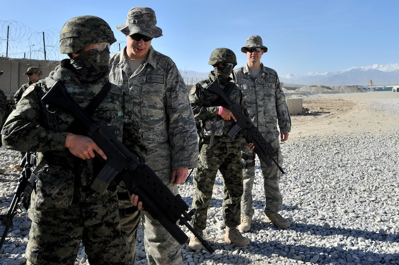 Senior Airman Gary Farmer (second from left) and Staff Sgt. Mason Flores, from the 455th Expeditionary Security Forces Squadron, supervise Staff Sgt. Jon Myung Jae (left) and Staff Sgt. Kim Tae Young, Republic of Korea army security forces, before firing a M203 grenade launcher at Bagram Airfield, Afghanistan, April 22, 2011. (U.S. Air Force photo by Senior Airman Sheila deVera)