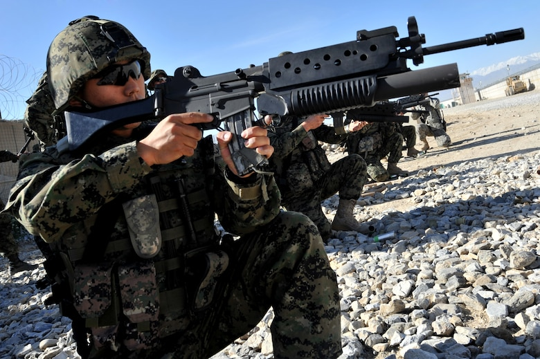Staff Sergeant Yoohyun Je, Republic of Korea Army security forces, takes position before firing a non-lethal 40-millimeter sponge round used in riot and crowd control at Bagram Airfield, Afghanistan, April 22, 2011. Sergeant Je and other security forces have to qualify on M203 grenade launcher before joining Bagram's base defense. (U.S. Air Force photo by Senior Airman Sheila deVera)