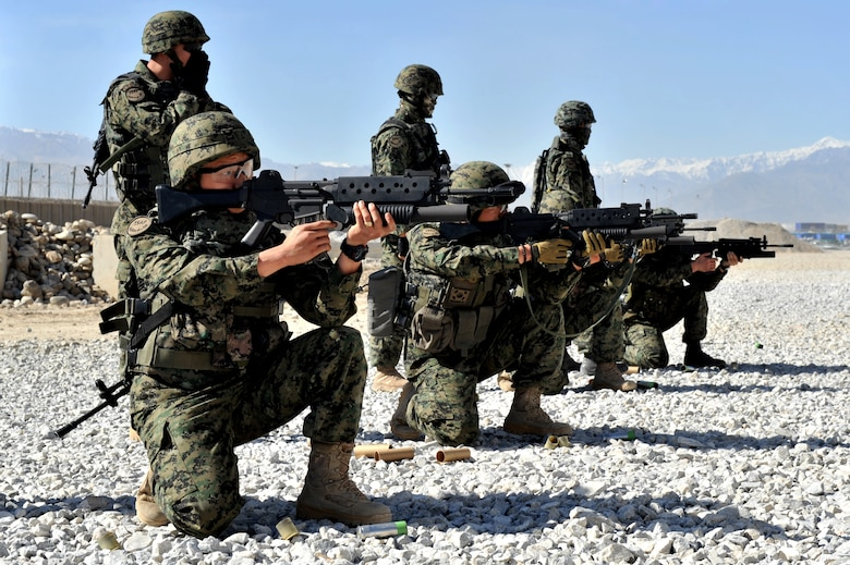 Soldiers from the Republic of Korea army take position before firing non-lethal munitions during escalation of force training at Bagram Airfield, Afghanistan, April 22, 2011. The soldiers have to qualify on M203 grenade launcher before joining Bagram's base defense. (U.S. Air Force photo by Senior Airman Sheila deVera)