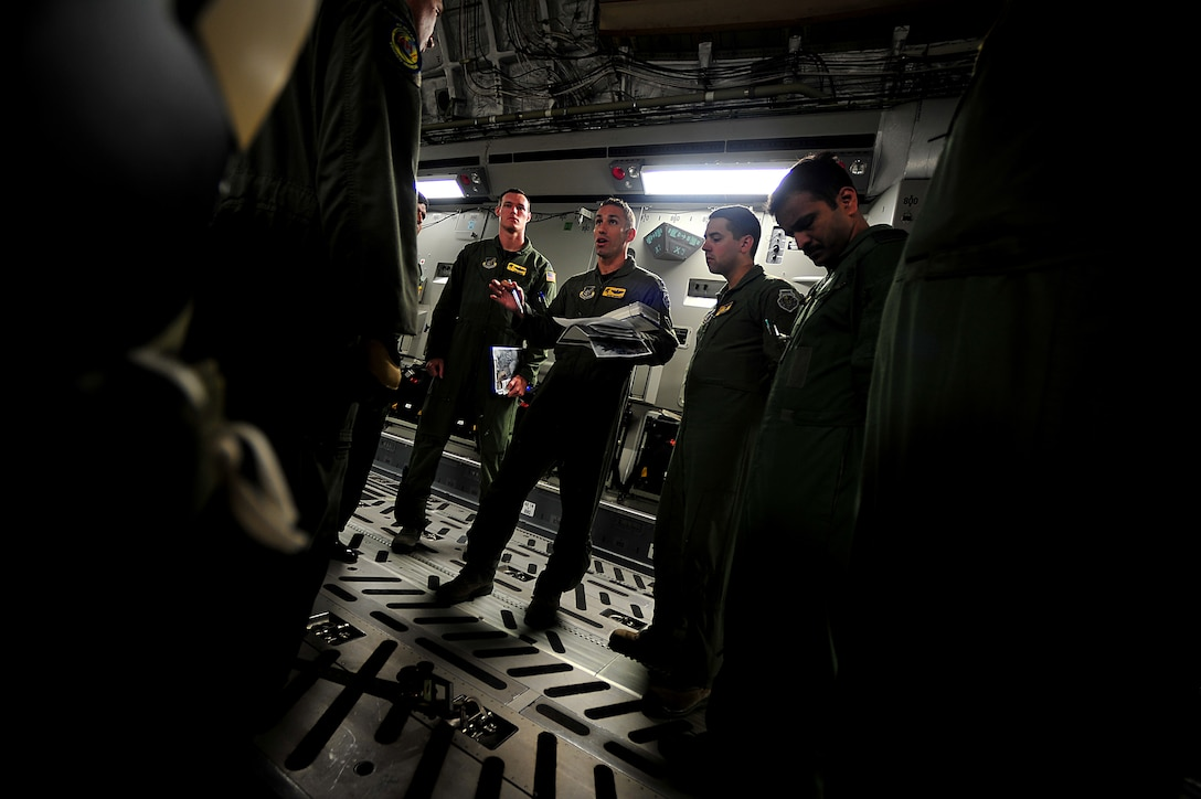 Crew members from Joint Base Pearl Harbor-Hickam, Hawaii, receive a pre-flight briefing during Air Mobility Rodeo 2011 at Joint Base Lewis-McChord, Wash., July 27. Air Mobility Rodeo is the U.S. Air Force's and Air Mobility Commandís premier international combat skill and flying operations competition designed to develop and improve techniques, procedures and interoperability, while optimizing international mobility partnerships and enhancing mobility operations. (U.S. Air Force photo/Staff Sgt. Nicholas Pilch)