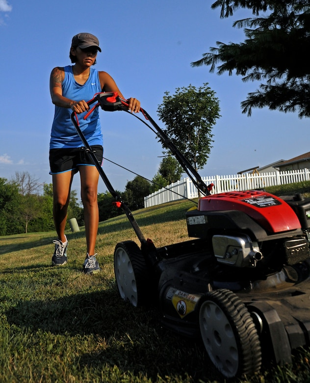WHITEMAN AIR FORCE BASE, Mo. - Gina Daniel, wife of Staff Sgt. Steven Daniel, 509th Maintenance Squadron, mowes her lawn July 28, 2011. The base housing office here recommends mowing as necessary to maintain a neat appearance. Specific requirements can be found in a brochure at the base housing office here. (U.S. Air Force photo by Airman 1st Class Cody H. Ramirez)