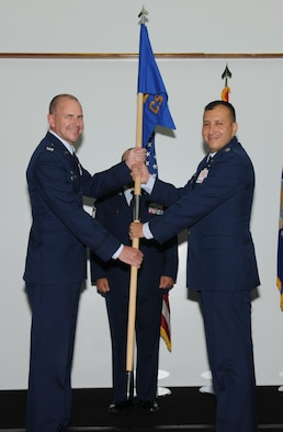 Col. Alan Wieder, former 36th Mission Support Group commander passes the 36th Communications Squadron guidon to Lt. Col. Freddie Rosas, newly appointed  36th Communications Squadron Commander, during a change of command ceremony here, July 7. (U.S. Air Force photo/Senior Airman Carlin Leslie)