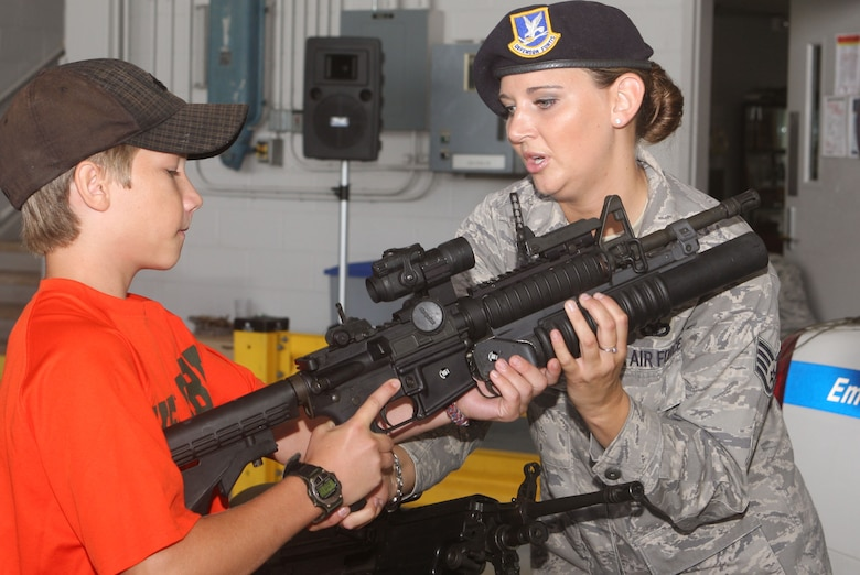 With assistance of Staff Sgt. Juanita Dahmen from the 94th Security Forces Squadron, family members felt what it was like to handle weapons used by security forces personnel. (U.S. Air Force Photo/Don Peek)