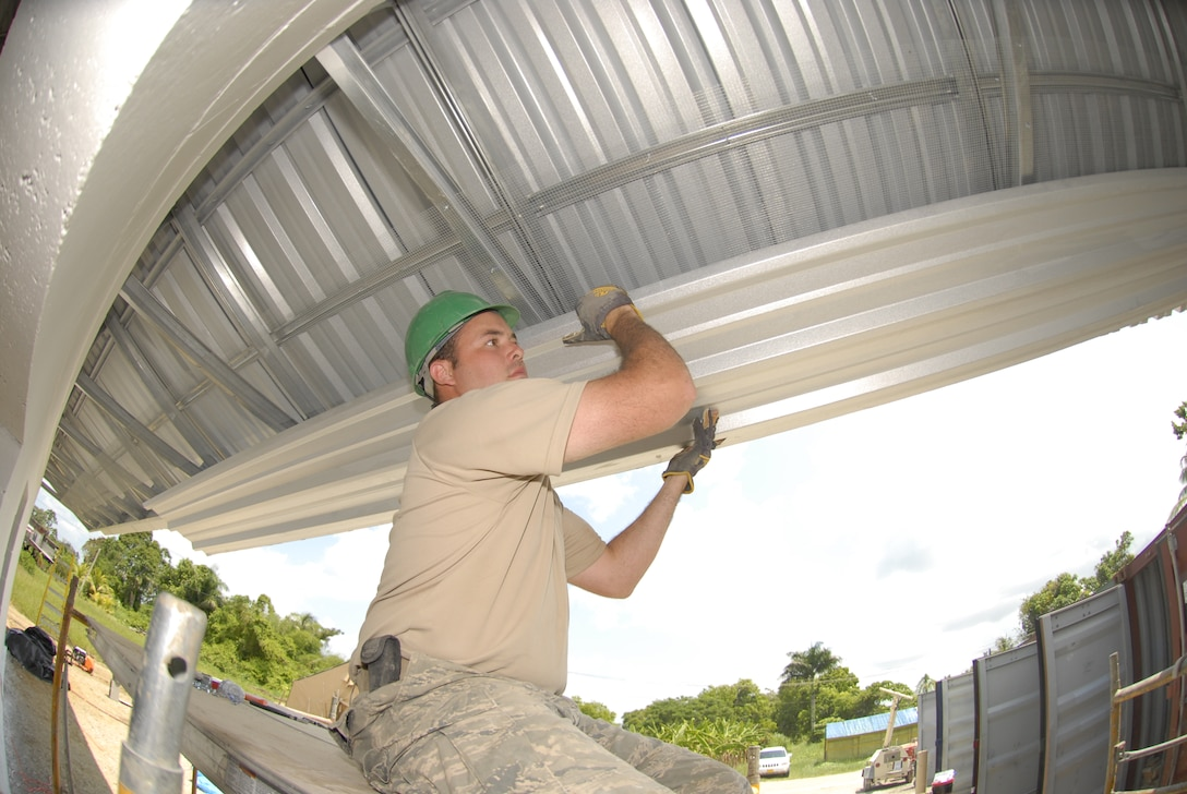PARAMARIBO, Suriname - Senior Airman Dane Miller, 114th Fighter Wing Civil Engineer Squadron, lifts a piece of corrugated metal into place for the soffits on the Alkmaar Clinic being built in the Commewijne district here July 6, 2011. New Horizons is a cooperative effort between the government of Suriname and the United States Southern Command. This exercise is scheduled to build two schools, two medical clinics, and three community parks. (Air Force Photo by Master Sgt. Christopher Stewart)(Released)