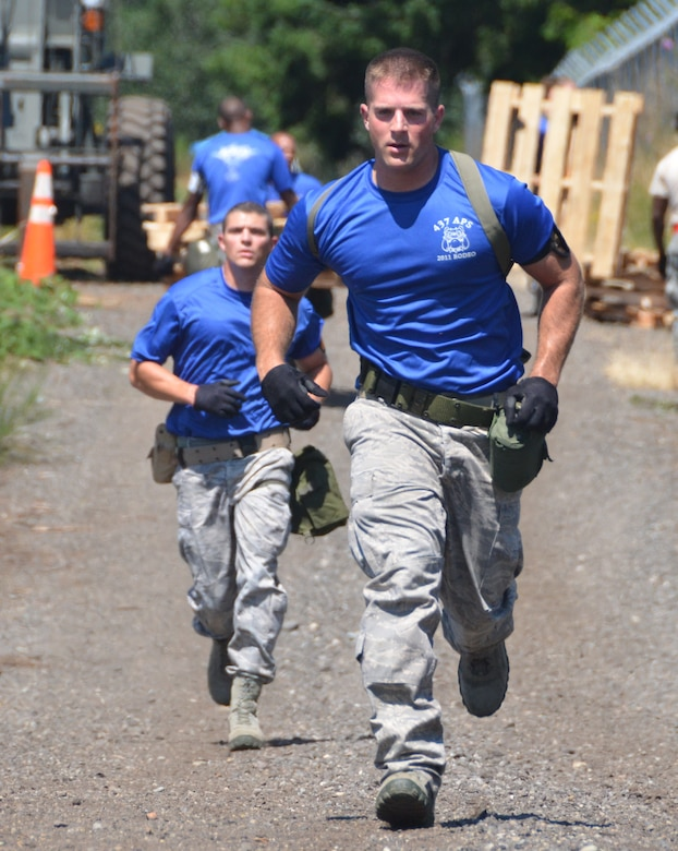 Staff Sgt. Nicholas Sansone (right) and Staff Sgt. Matthew Lumm, run during an aerial port obstacle course, July 28, 2011, at Joint Base Lewis-McChord, Wash. The course was part of Air Mobility Rodeo 2011, a biennial international competition that focuses on mission readiness, featuring airdrops, aerial refueling and other events that showcase the skills of mobility crews from around the world. Sansone and Lumm are air transportation specialist from the 437th Aerial Port Squadron. (U.S. Air Force photo /2nd Lt. Susan Carlson)