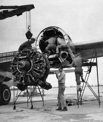 Maintenance personnel in India removing a damaged engine from a B-29.  They took off any undamaged parts and reused them on the replacement engine. (U.S. Air Force photo).