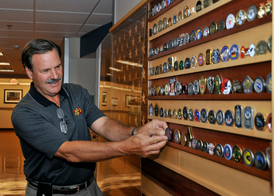 Robert M. Simpson, Jr. Jelly Belly Candy Company President and Chief Operating Officer, adds a coin to the collection at the 779th Aeromedical Staging Facility after receiving a tour here July 13. Simpson and Herman G. Rowland Sr., Jelly Belly Candy Company Chairman of the Board, participated in the Andrews Leadership Series, an initiative spearheaded by Col. Kenneth Rizer, 11th Wing/Joint Base Andrews commander. The series showcases high profile military and civic members who are leaders in their respective field. The program also aims to educate servicemembers about the characteristics of being a leader and provides JBA members with the tools they need to become better leaders themselves. (U.S. Air Force photo/Senior Airman Laura Turner)