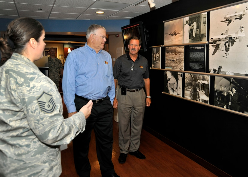Master Sgt. Michelle Tancrede, NCO in charge of mission operations, 779th Aerospace Medicine Squadron, shows Robert M. Simpson Jr., Jelly Belly Candy Company President and Chief Operating Officer, and Herman G. Rowland Sr., Jelly Belly Candy Company Chairman of the Board, the Heritage Wall during their tour of the 779th Aeromedical Staging Facility here July 13. Simpson and Rowland participated in the Andrews Leadership Series, an initiative spearheaded by Col. Kenneth Rizer, 11th Wing/Joint Base Andrews commander. The series showcases high-profile military and civic members who are leaders in their respective field. The program also aims to educate servicemembers about the characteristics of being a leader and provides JBA members with the tools they need to become better leaders themselves. (U.S. Air Force photo/Senior Airman Laura Turner)