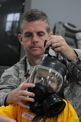 """Tech. Sgt. David Flesch helps his daughter, Morgan Flesch, try on the MCU-2 Protective Mask used to protect against chemical and biological warfare agents. Members of the 126th Air Refueling Wing, located at Scott AFB, Ill., brought their children to work for a """"Kids on Guard"""" day that lets children experience duties and training events that Illinois Air National Guard personnel go through on a regular basis. (U.S. Air Force photo by Master Sgt. Ken Stephens.)"""