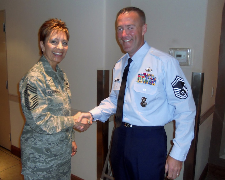 U.S. Air Force Command Chief Master Sgt. Denise Jelinski-Hall, Air Force Senior Enlisted Advisor hands Oregon Air National Guard Senior Master Sgt. Christopher Roper, one of her coins prior to his graduation ceremony from the U.S. Army Sergeant Major Academy on June 17, 2011 at Ft. Bliss, Tex. (Photograph courtesy of Senior Master Sgt. Christopher Roper)