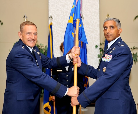 """SCOTT AIR FORCE BASE, Ill. -- Lt. Gen. Michael Basla, vice commander of Air Force Space Command, presents the Air Force Network Integration Center guidon to its new commander, Col. Rizwan """"Riz"""" Ali, during a change of command ceremony Aug. 3.  AFNIC is the Air Force's technical center of excellence for Air Force network integration.   (U.S. Air Force photo/ Airman 1st Class Divine Cox)"""