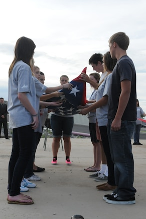 Delegates unfold the flag during a flag retirement ceremony during Freedom Academy at Camp Williams.  High school students from across the state get the opportunity to spend a week learning about freedoms and opportunities they have. (U.S. Army photo by Private 1st Class Ariel J. Solomon)