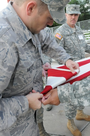Air Force Staff Sgt. Seth Mayer helps fold the flag after a flag ceremony held during Freedom Academy.  Each morning, students participated in raising the flag and reciting the pledge of allegience as they spent the week learning more about the meaning of freedom.  (U.S. Army photo by Sgt. Shana Hutchins)