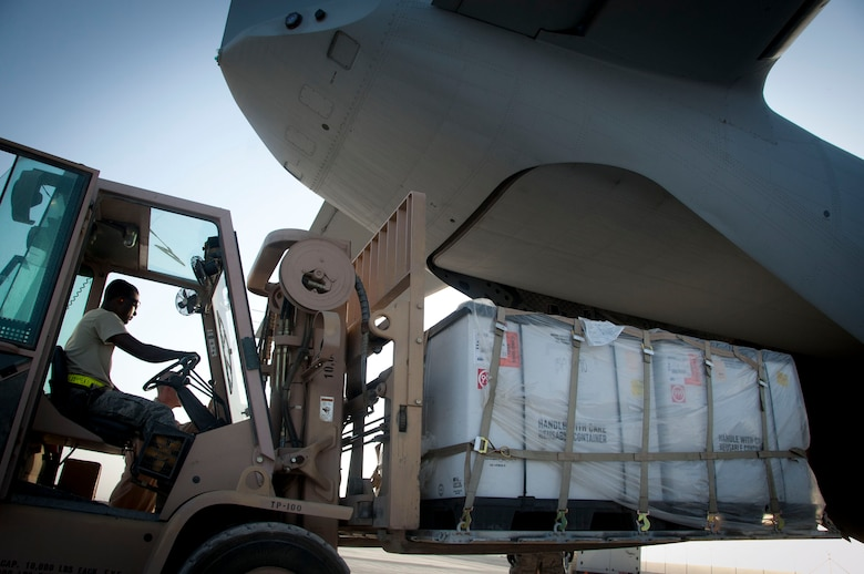 Senior Airman Theophilus Okrah, 451st Expeditionary Logistics Readiness Squadron ramp services member, loads cargo into a C-27 at Kandahar Air Field, Afghanistan, Aug. 3, 2011. The C-27s belong to the 702 Air Expeditionary Squadron.(U.S. Air Force photo by Senior Airman Corey Hook)