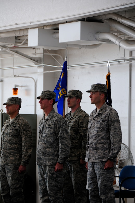 Col. Sami Said, 144th Fighter Wing Commander, along with Col. Clay Garrison and Col. Mark Favetti prepare for the exchange of the group guidon during the 144th Maintenace groups change of command ceremony. Col. Mark Favetti assumed  command of the 144th Maintenance group from col. Garrison during the ceremony August 7 2011.