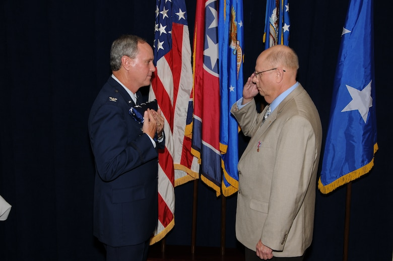 Colonel Harry D. Montgomery, 164th Airlift Wing Commander, presents the American Flag that was flown on Colonel Spencer's last duty day to Lieutenant Colonel Lamar Spencer during Col Spencer's retirement ceremony.