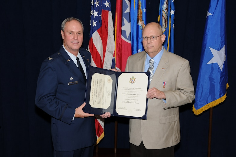 Colonel Harry D. Montgomery, 164th Airlift Wing Commander, presents the Certificate of Retirement to Lieutenant Colonel Lamar Spencer during Col Spencer's retirement ceremony.