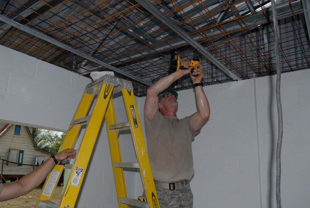 PARAMARIBO, SURINAME - Master Sgt. Mike Clausen, 1st Sgt. for the 114th Fighter Wing Civil Engineer Squadron, helps hang a piece of ridge brace at the Alkmaar Clinic being built in the Commewijne district here July 13, 2011.  The clinic is being built in support of the New Horizons 2011 exercise.   (Air Force Photo by Tech. Sgt. Quinton Young)(RELEASED) USAF