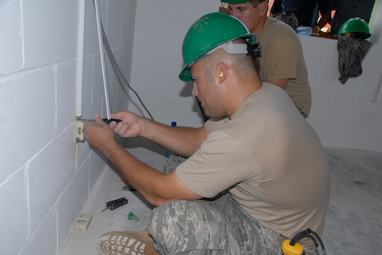 PARAMARIBO, SURINAME - Staff Sgt. Zach Jorgensen, a craftsman with the 114th Fighter Wing's Civil Engineer Squadron,  shows Senior Airman Andrew Peterson how to install an electrical outlet in the Alkmaar Clinc being built in the Commewijne district here July 13, 2011.  The 114th is helping build one of  two clinics that are scheduled to be built during New Horizons Suriname.  (Air Force Photo by Tech. Sgt. Quinton Young)(RELEASED) USAF