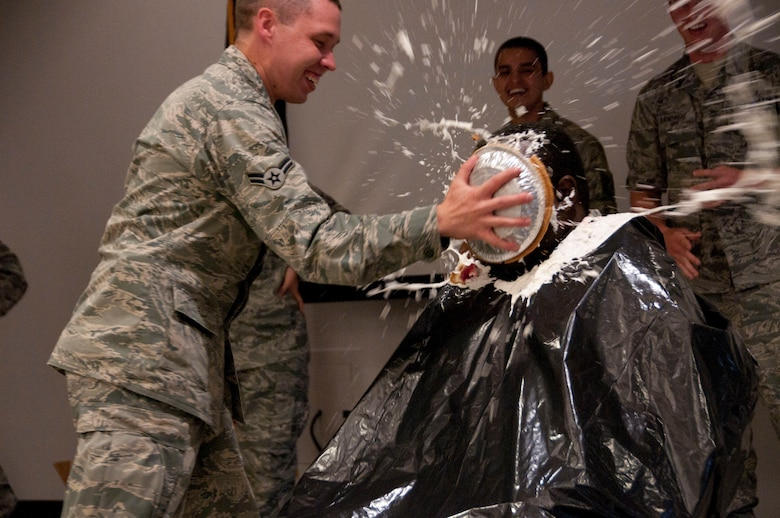 """Chief Master Sgt. Bill Minter gets a pie in the face Aug. 6 from Airman 1st Class Michael Labreque. The 162nd Fighter Wing Junior Enlisted Council and wing senior leaders worked together on the """"Pie in the Face"""" fund raising event to benefit several worthy JEC programs. (U.S. Air Force photo/Master Sgt. Dave Neve)"""