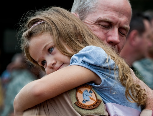 Lt. Col. Thomas Frazier of the 711th Special Operations Squadron receives a overdue hug from his daughter after returning from a deployment to Southwest Asia, Aug. 7.  More than 25 Air Force Reserve Airmen were welcomed back home at a homecoming party at Duke Field.  (U.S. Air Force photo/Tech. Sgt. Samuel King Jr.)