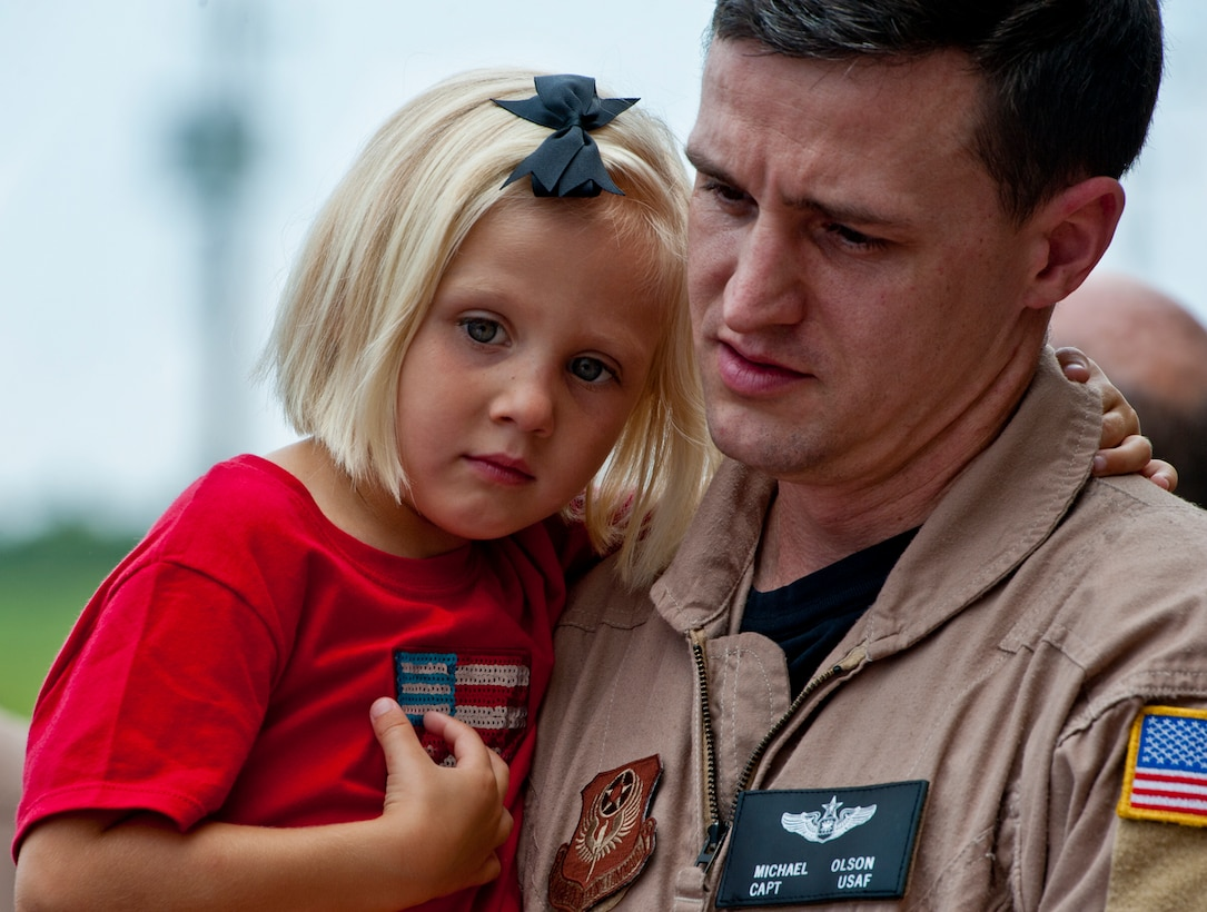 Capt. Michael Olson of the 711th Special Operations Squadron, keeps his 4-year-old daughter, Lillian, in his arms after returning from a deployment to Southwest Asia, Aug. 7.  Olson, along with 25 other Air Force Reserve Airmen were welcomed back at a homecoming party at Duke Field.  (U.S. Air Force photo/Tech. Sgt. Samuel King Jr.)