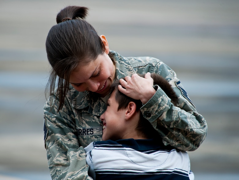 Master Sgt. Adriana Torres of the 711th Special Operations Squadron, admires her smiling son upon her return from a deployment to Southwest Asia, Aug. 7.  More than 25 Air Force Reserve Airmen were welcomed back home at a homecoming party at Duke Field.  (U.S. Air Force photo/Tech. Sgt. Samuel King Jr.)