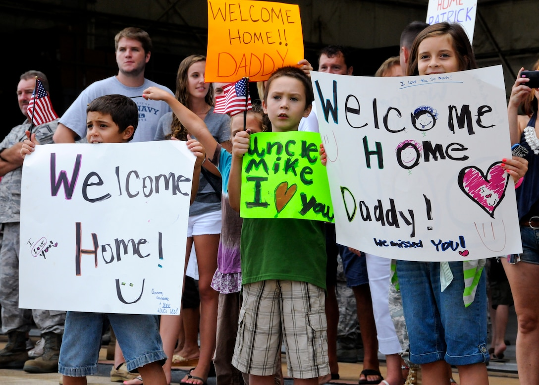 Children hold up signs as Air Force Reservists make their way to greet their family after a deployment to Southwest Asia, Aug. 7.  More than 25 Airmen were welcomed back home at a homecoming gathering at Duke Field.  (U.S. Air Force photo/Tech. Sgt. Cheryl Foster)