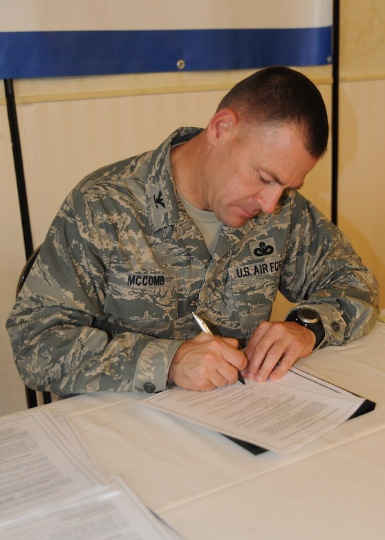 Col. Richard McComb signs his lease to live in privatized base housing at the Charleston Club at Joint Base Charleston - Air Base Aug. 5. Forest City Military Communities, which manages JB CHS- AB housing, held the lease signing event and encouraged all residents to stop by the Charleston Club and sign their leases. The transition to privatized housing takes place Oct.1. McComb is the Joint Base Charleston commander. (U.S. Air Force photo/ Airman 1st Class Ashlee Galloway)