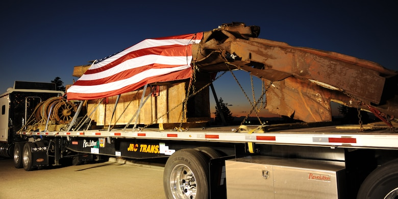 BUCKLEY AIR FORCE BASE, Colo. --  A flag drapes pieces of steel from the top five floors of the World Trade Center Aug. 7, 2011. Resting at Buckley AFB, pieces from the Port Authority of New York and New Jersey are being transported across the nation to commemorate the 10th anniversary of 9/11. (U.S. Air Force photo by Senior Airman Marcy Glass)
