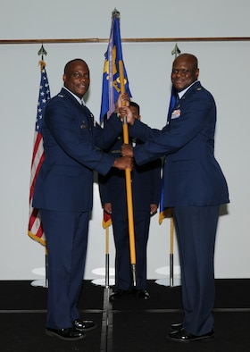 Col. Dwayne Thomas (left), 36th Mission Support Group commander, passes the 36th Force Support Squadron guidon to Maj. Craig Smalls, newly appointed 36 FSS commander, during a change of command ceremony here July 19.(U.S. Air Force photo/ Senior Airman Carlin Leslie)