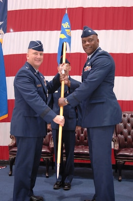 Brig. Gen. John Doucette (left), 36th Wing commander, passes the 36th Mission Support Group guidon to Col. Dwayne Thomas, newly appointed 36 MSG commander, during a change of command ceremony here July 12.(U.S. Air Force photo/ Senior Airman Carlin Leslie)