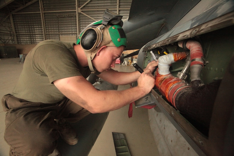Lance Cpl. Benjamin Johnson, a Marine Attack Squadron 513 avionics technician and Blanchard, Okla., native, puts back a fuel level amplifier on one of the squadron's AV-8B Harriers in the squadron's hangar at Kandahar Airfield, Afghanistan, Aug. 9.