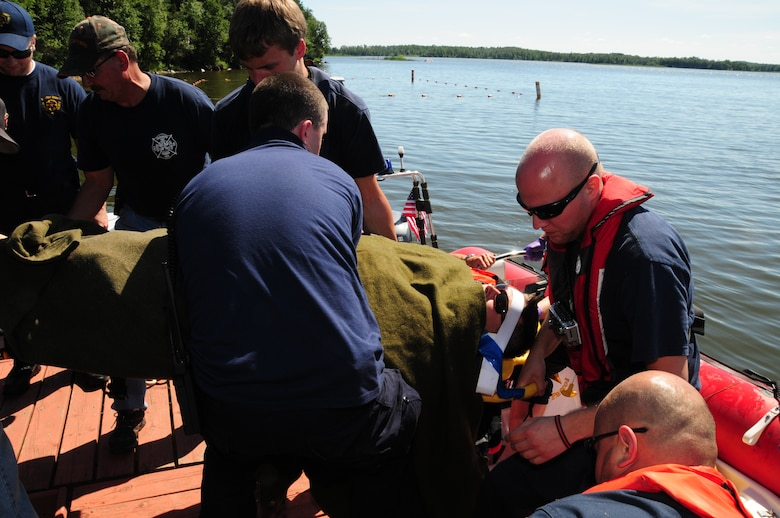 Members of the St. Louis County Rescue Squad and Fredenberg Rescue Squad lift the recovered 148th Fighter Wing pilot safely to shore after transport across Fish Lake July 11, 2011.  Throughout the pilot's ride across the lake, members of the St. Louis County Rescue Squad simulated medical treatment and coordinated with their counterparts back on shore.  (U.S. Air Force photo by Tech. Sgt. Scott G. Herrington)