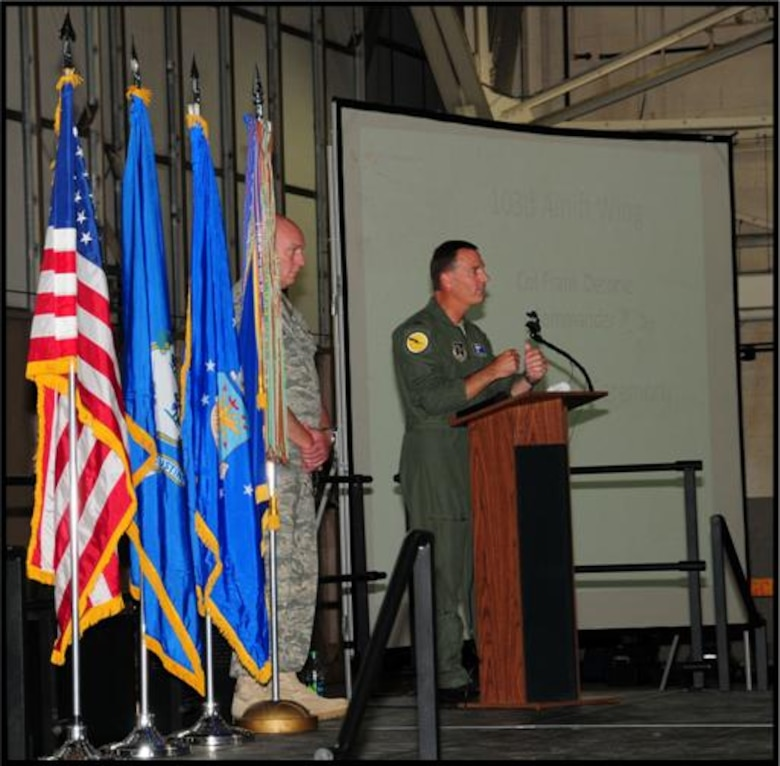 Wing Command Chief Master Sgt. Edward Gould looks on as Col. Frank Detorie, 103rd Airlift Wing commander, addresses Flying Yankee members, family, friends and guests gathered to recognize 2010's outstanding performers June 4, 2011, in the main hangar at Bradley Air National Guard Base, East Granby, Conn. (U.S. Air Force photo by Airman 1st Class Emmanuel Santiago)