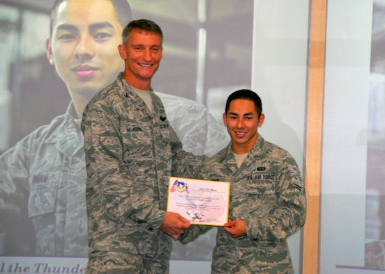 Col. Patrick McKenzie, 51st Fighter Wing commander, awards Airman 1st Class Fa Pham, 51st Force Support Squadron, with a certificate recognizing him as the Airman Spotlight of the week August 9, 2011. (U.S. Air Force photo/Senior Master Sgt. Stuart Camp)